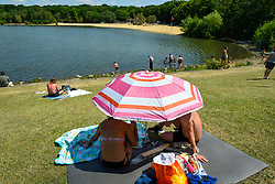 © Licensed to London News Pictures. 01/06/2020. LONDON, UK.  People sunbathe adjacent to the beach (seen in the distance) at Ruislip Lido in north west London.  Hillingdon Council has closed the beach to the public following several days where the public were not adhering to social distancing as coronavirus pandemic lockdown restrictions have been eased by the UK government.  On the first day of the meteorological summer, visitors who travelled from out of the area resorted to finding a place to sunbathe on any patch of grass they could find.  Photo credit: Stephen Chung/LNP