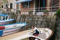 """PISCIOTTA, ITALY - 22 APRIL 2018: A man paints his boat near the harnour of Pisciotta, Italy, on April 22nd 2018.<br /> <br /> Former restaurant owners Donatella Marino and her husband Vittorio Rimbaldo have spent the recent years preparing and selling salted anchovies, called alici di menaica, to a growing market thanks to a boost in visibility from the non-profit Slow Food.  The ancient Menaica technique is named after the nets they use brought by the Greeks wherever they settled in the Mediterranean. Their process epitomizes the concept of slow food, and involves a nightly excursion with the special, loose nets that are built to catch only the larger swimmers. The fresh, red anchovies are immediately cleaned and brined seaside, then placed in terracotta pots in between layers of salt, to rest for three months before they're aged to perfection.While modern law requires them to use PVC containers for preserving, the government recently granted them permission to use up to 10 chestnut wood barrels for salting in the traditional manner. The barrels are """"washed"""" in the sea for 2-3 days before they're packed with anchovies and sea salt and set aside to cure for 90 days. The alici are then sold in round terracotta containers, evoking the traditional vessels that families once used to preserve their personal supply.<br /> <br /> Unlike conventional nets with holes of about one centimeter, the menaica, with holes of about one and half centimeters, lets smaller anchovies easily swim through. The point may be to concentrate on bigger specimens, but the net also prevents overfishing."""