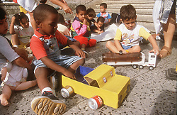 Nursery school children playing with toys in playground,