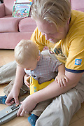 Toddler helping dad insert batteries into child's game age 1 and 32. Balucki District Lodz Central Poland