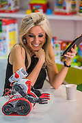 A woman enjoys playing with the app controlled music funtion of a build yourself Evolution Robot, by Clementoni - The London Toy Fair opens at Olympia exhibition centre. Organised by the British Toy and Hobby Association it is the only dedicated toy, game and hobby trade exhibition in the UK. It runs for three days, with more than 240 exhibiting companies ranging from the large internationals to the new start up companies.