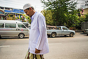 """11 JANUARY 2013 - BANGKOK, THAILAND:    A Thai Muslim man walks to mosque in the Ban Krua neighborhood in Bangkok. The Ban Krua neighborhood of Bangkok is the oldest Muslim community in Bangkok. Ban Krua was originally settled by Cham Muslims from Cambodia and Vietnam who fought on the side of the Thai King Rama I. They were given a royal grant of land east of what was then the Thai capitol at the end of the 18th century in return for their military service. The Cham Muslims were originally weavers and what is known as """"Thai Silk"""" was developed by the people in Ban Krua. Several families in the neighborhood still weave in their homes.                  PHOTO BY JACK KURTZ"""