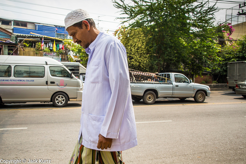 "11 JANUARY 2013 - BANGKOK, THAILAND:    A Thai Muslim man walks to mosque in the Ban Krua neighborhood in Bangkok. The Ban Krua neighborhood of Bangkok is the oldest Muslim community in Bangkok. Ban Krua was originally settled by Cham Muslims from Cambodia and Vietnam who fought on the side of the Thai King Rama I. They were given a royal grant of land east of what was then the Thai capitol at the end of the 18th century in return for their military service. The Cham Muslims were originally weavers and what is known as ""Thai Silk"" was developed by the people in Ban Krua. Several families in the neighborhood still weave in their homes.                  PHOTO BY JACK KURTZ"
