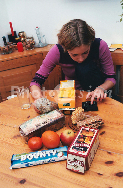 Teenage girl working out calorie content of different foods