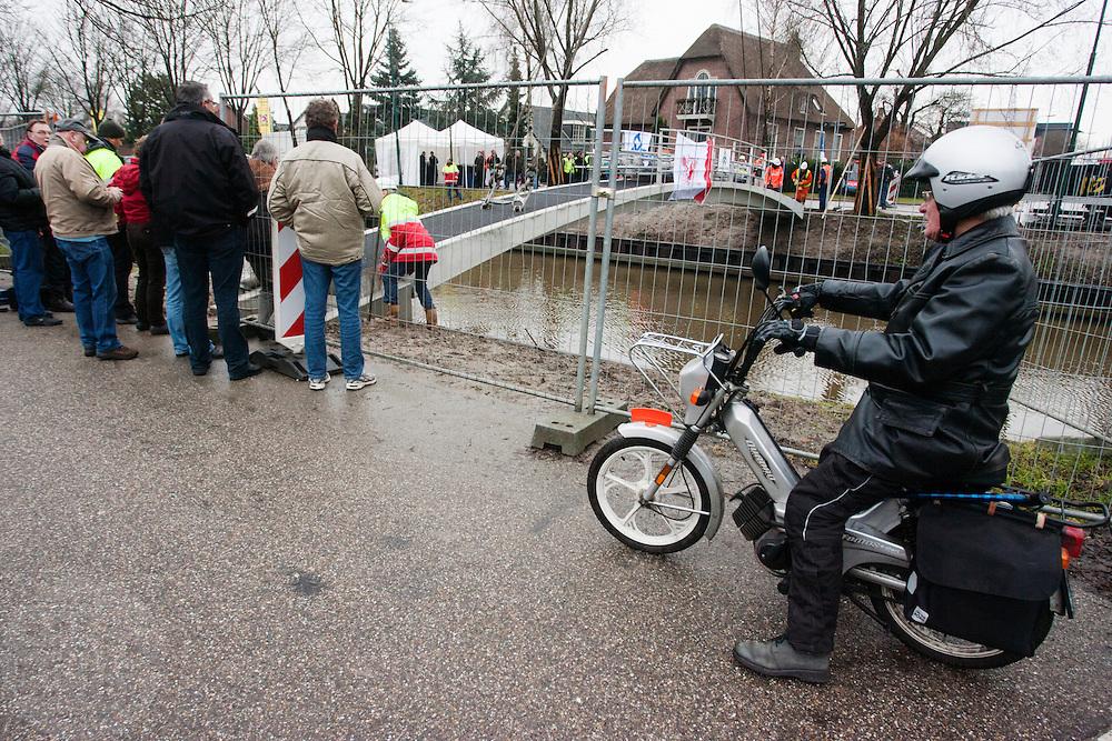 Een man op een brommer kijkt hoe een speciale fietsbrug over de Leidsche Rijn in Utrecht wordt geplaatst.<br /> <br /> A man on a moped is watching how a special bridge for cyclists is being placed over the Leidsche Rijn near Utrecht