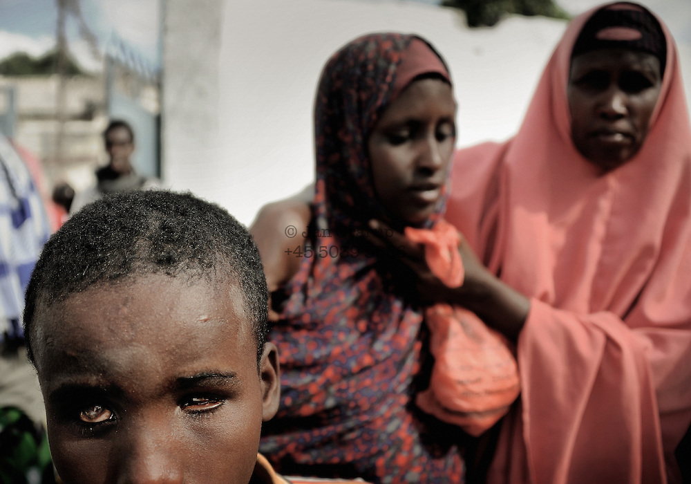 A boy blinded by a bomb and his mentally sick sister at a food handout in the center of the city.Death or Play. Women&acute;s Basketball in Mogadishu<br /> Women's basketball? In Europa and the U.S., we take it for granted. But consider this: In Mogadishu, war-torn capital of Somalia, young women risk their lives every time they show up to play.<br /> Suweys, the captain of the Somali women&acute;s basketball team, and her friends play the sport of the deadly enemy, called America. This is why they are on the hit list of the killer commandos of Al Shabaab, a militant islamist group, that has recently formed an alliance with the terrorist group Al Qaeda and control large swathes of Somalia.<br /> <br /> Al Shabaab, who sets bombs under market stands, blows up cinemas, and stones women, has declared the female basketball players &bdquo;un-islamic&ldquo;. One of the proposed punishments is to saw off their right hands and left feet. Or simply: shoot them.<br /> <br /> Suweys&acute; team trains behind bullet-ridden walls, in the ruins of the failed city of Mogadishu &ndash; protected by heavily armed gun-men. The women live in constant fear of the islamist killer commandos. Stop playing basketball? Never, they say.<br /> Women&acute;s basketball in the world&acute;s most dangerous capital. Female basketball in Mogadishu, Somalia.<br /> A deadly game..