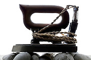 vintage electric hot iron placed on pebble stones