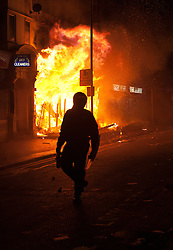 © Licensed to London News Pictures. 09/08/2011 LONDON, UK. A police officer walks past the front of a blazing shop on London Road in Croydon after it was set alight by looters.  Croydon was one of several London boroughs and English cities hit by a third night of rioting and looting. Photo credit: Matt Cetti-Roberts/LNP