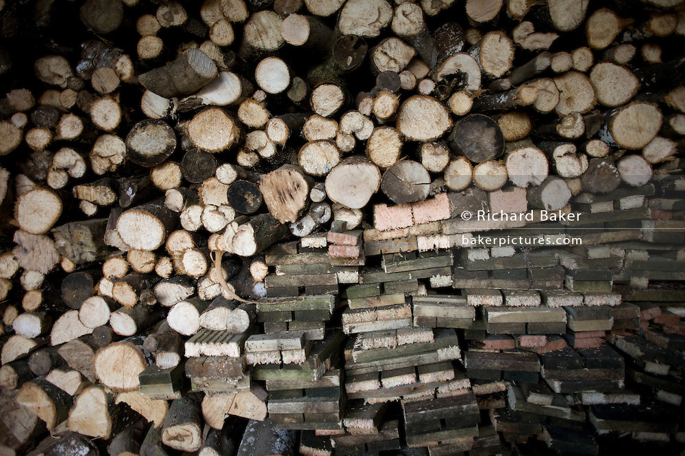 Piles of sawn logs, ready for a winter home fire, stays dry under cover on a small holding.