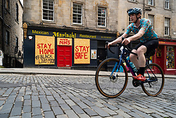 Edinburgh, Scotland, UK. 16 June, 2020. As shops open in England, Scottish shops and businesses remain closed, Streets are empty and pubs and shops are still closed with many boarded up. Bars might be allowed to open outside areas at end of week but currently they are only-permitted  to serve drinks to takeaway. Pictured; Cyclist rides past boarded up restaurant on Victoria Street  Iain Masterton/Alamy Live View.