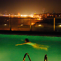 Local woman swimming in the rooftop pool of a five star hotel with Marine drive lit up behind.