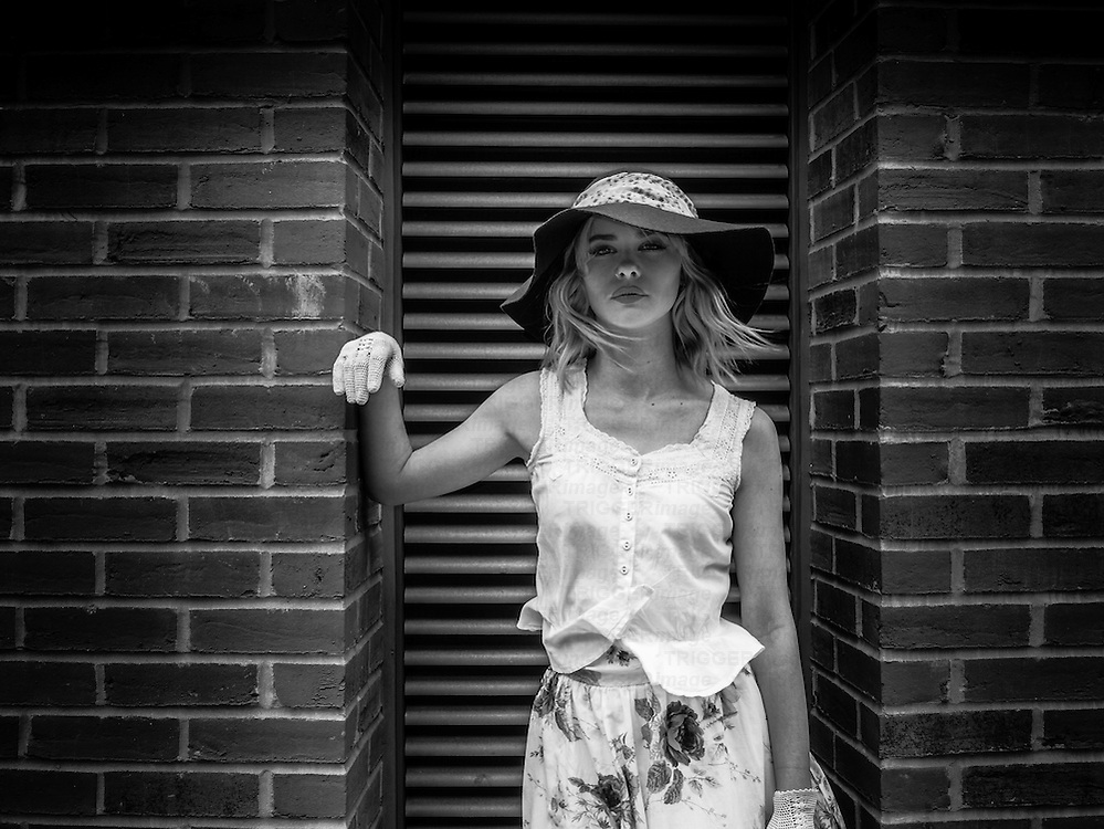 Blonde female model with hat in the street