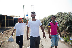 © Licensed to London News Pictures. 30/08/2015. Calais, France. Three men carry water and supplies through the refugee camp in Calais, also known as the Jungle. Tomorrow the French PM, Manuel Valls, will visit the day centre Jules Ferry at the camp. Photo credit : Isabel Infantes/LNP