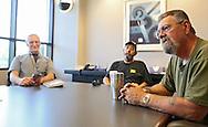 Richard Hrvol (from left), of Cedar Rapids and Jay Kaiser, of Cedar Rapids, listen as Doug Adamson, of Center Point, talks about the proposed veterans center at Wells Fargo Bank in Cedar Rapids on Tuesday, July 16, 2013.