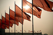 The sun rises over a group of red flags on Tiananmen Square.