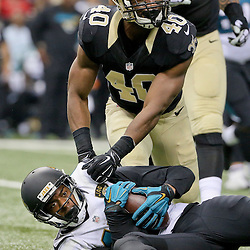 Dec 27, 2015; New Orleans, LA, USA; New Orleans Saints cornerback Delvin Breaux (40) tackles Jacksonville Jaguars wide receiver Allen Robinson (15) during the second quarter of a game at the Mercedes-Benz Superdome. Mandatory Credit: Derick E. Hingle-USA TODAY Sports