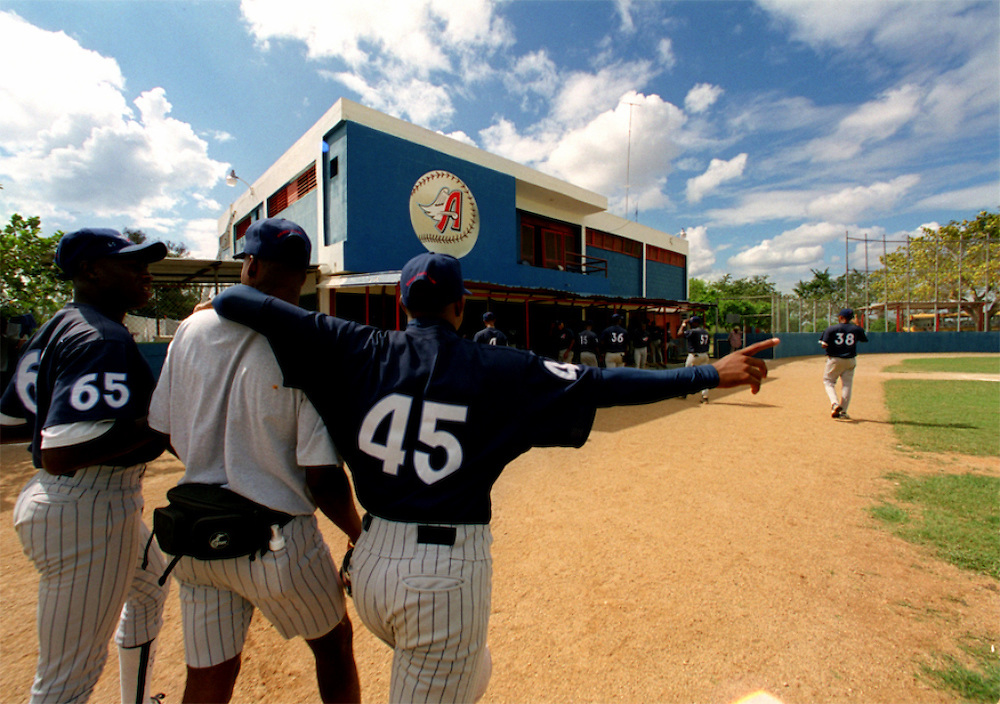 024222.SP.0114.angels5.kc--San Pedro de Macoris, Dominican Republic--Players and trainer(middle) leave the field after  a day game between the Anaheim Angels Academy Team and the Boston Red Sox Academy Team. At a young age Dominican boys learn that baseball could be their chance to make it in the big leagues. The little league baseball system is mostly disorganized but the baseball academies run by MLB teams provides an all around learning experience for boys once they reach sixteen.