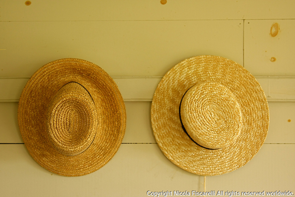 Two natural straw shaker hats hang on the wall.