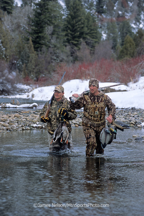 34-693. Duck hunters walk along a side channel of the South Fork of the Snake River in Idaho during a winter day.
