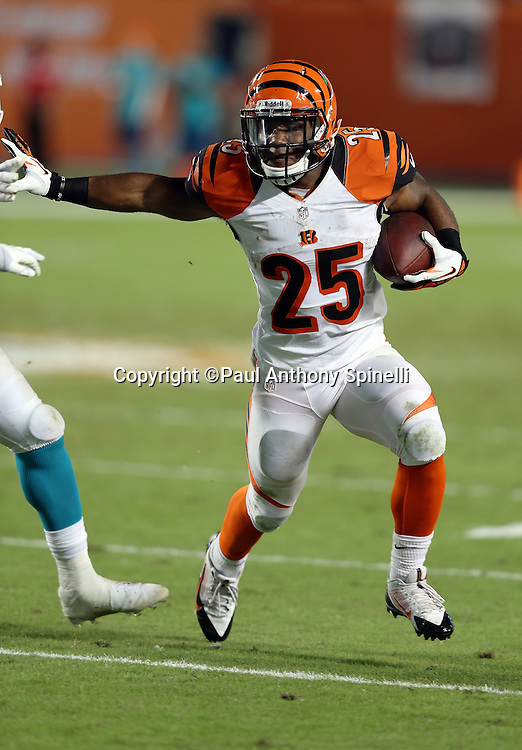 Cincinnati Bengals running back Gio Bernard (25) straight arms a defender as he runs with the ball after catching a flat pass for a third quarter gain of six yards during the NFL week 9 football game against the Miami Dolphins on Thursday, Oct. 31, 2013 in Miami Gardens, Fla.. The Dolphins won the game 22-20 in overtime. ©Paul Anthony Spinelli