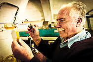 The owner of this olive press mill, examines the fresh olive oil, for acidity and consistency.