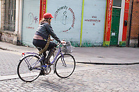 Woman cycling past Amnesty International shop and offices in Dublin Ireland
