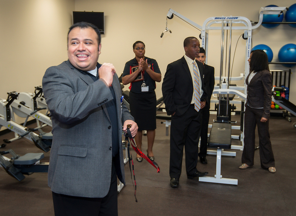 Hartman Middle School principal Geovanny Ponce shows off the new workout room during the dedication of the school's Health and Medical wing, April 3, 2014.