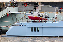 © Licensed to London News Pictures. 16/09/2019. London, UK. A person mops the decks on luxury superyacht Ocean Dreamwalker III which is moored next to HMS Belfast on the River Thames, seen with a helicopter on the helipad at the stern of the yacht during a London visit. 155 feet long long Ocean Dreamwalker III was built in 2018 and is rumoured to be owned by John Deng, a Chinese entrepreneur and politician. It is believed that this is the first time a superyacht has visited the capital with a helicopter onboard. Photo credit: Vickie Flores/LNP