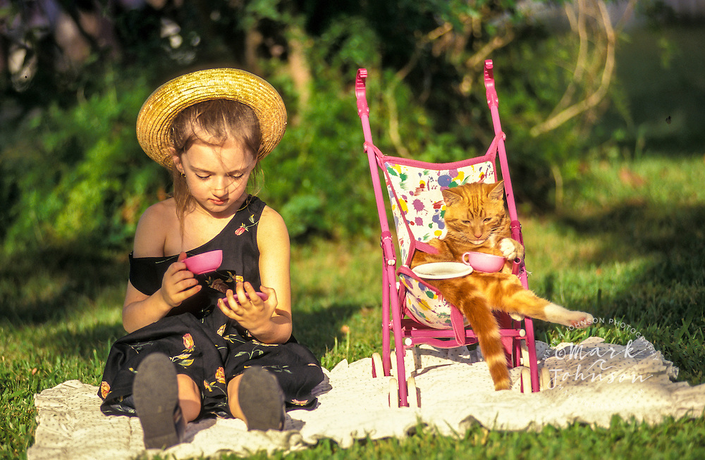 Girl having tea party with her pet cat.