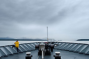 A lone passenger looks out at the shoreline from an Alaska Marine Highway System ferry en route to Gustavus, Alaska, June 21, 2017. <br /> Photo by David Lienemann