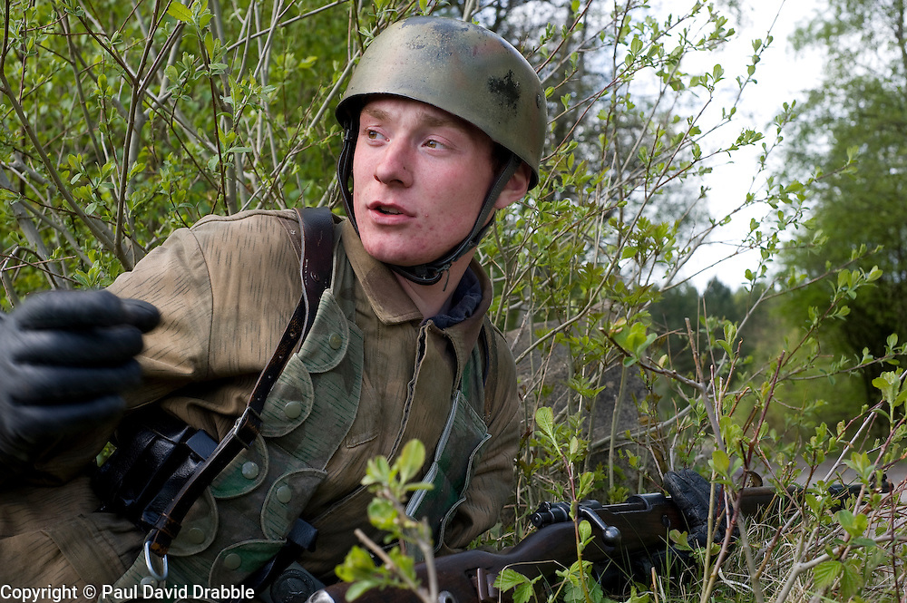 Reenactor from Northern World War Two Association, dressed as a member of the 1st Fallschirmjaeger Division 'The Green Devils' and holding a k98 bolt action rifle prepares an ambush for allied troops during a private 24hr exercise at Sutton Grange, near Ripon Yorkshire 15  May 2010 .Images © Paul David Drabble.