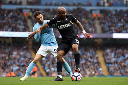 Swansea City's Andre Ayew (right) and Manchester City's Bernardo Silva battle for the ball during the Premier League match at the Etihad Stadium, Manchester.