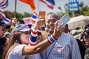 05 JANUARY 2014 - BANGKOK, THAILAND: SUTHEP THAUGSUBAND, leader of the anti-government movement, poses for pictures with girls and their smart phones during a march through Bangkok Sunday. Suthep is a former Deputy Prime Minister and member of the opposition Democrat Party who resigned to organize the protests against the Pheu Thai government.  He led the protestors on a march through the Chinatown district of Bangkok. Tens of thousands of people waving Thai flags and blowing whistles gridlocked what was already one of the most congested parts of the city. The march was intended to be a warm up to their plan by protestors to completely shut down Bangkok starting Jan. 13.     PHOTO BY JACK KURTZ