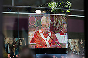 The Pope leads the Mass seen on a giant TV seen through a Monsson shop windpw during Benedict XVI's papal tour of Britain 2010, the first visit by a pontiff since 1982. Taxpayers footed the £10m bill for non-religious elements, which largely angered a nation still reeling from the financial crisis. Pope Benedict XVI is the head of the biggest Christian denomination in the world, some one billion Roman Catholics, or one in six people. In Britain there are about five million Catholics but only a quarter of Catholics regularly attend Sunday Mass and some churches have closed owing to spending cuts.