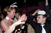 A girl dressed as a Playboy bunny watching a man dancing in a trilby hat Garlands, Liverpool, UK, 2002