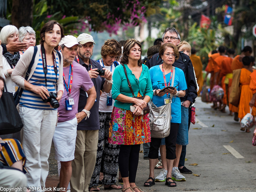 """12 MARCH 2016 - LUANG PRABANG, LAOS: Tourists watch Buddhist monks during the morning tak bat in Luang Prabang. Luang Prabang was named a UNESCO World Heritage Site in 1995. The move saved the city's colonial architecture but the explosion of mass tourism has taken a toll on the city's soul. According to one recent study, a small plot of land that sold for $8,000 three years ago now goes for $120,000. Many longtime residents are selling their homes and moving to small developments around the city. The old homes are then converted to guesthouses, restaurants and spas. The city is famous for the morning """"tak bat,"""" or monks' morning alms rounds. Every morning hundreds of Buddhist monks come out before dawn and walk in a silent procession through the city accepting alms from residents. Now, most of the people presenting alms to the monks are tourists, since so many Lao people have moved outside of the city center. About 50,000 people are thought to live in the Luang Prabang area, the city received more than 530,000 tourists in 2014.       PHOTO BY JACK KURTZ"""