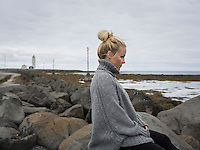 Young blond woman sitting by Grotta with lighthouse in the back