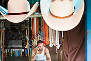 July 25 - PHOENIX, AZ: JOSE ALVAREZ makes a phone call while he waits for customers in his shop selling cowboy boots and hats in El Gran Mercado. El Gran Mercado (The Big Market) in Phoenix is the largest flea market in the Phoenix area and has served the area's immigrant community for more than 20 years. With more than 150 small independent stalls selling Mexican clothes, cowboy hats, Mariachi music and food stalls selling Mexican favorites like birria chivo (goat stew) and menudo (tripe) it was more like a Mexican market than an American mall. Business in the mercado is down more than half this year because many immigrant families, legal and illegal, are leaving Arizona before the state's tough new anti-immigrant law, SB 1070 goes into effect on July 29. SB 1070 allows local police officers to check the immigration status of people they have probable cause to believe may be in the US illegally and requires immigrants to carry their immigration papers with them at all times.    Photo by Jack Kurtz
