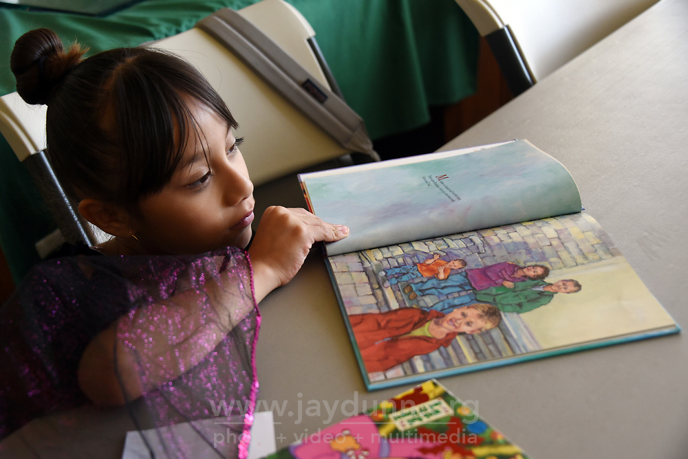 During reading time at LIFE's after-school program,  Alexandra Ruiz makes a quiet space for herself around a table.