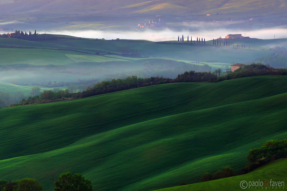 The rolling hills nearby San Quirico d'Orcia, as seen from the vantage point known as Belvedere d'Orcia, on a misty morning of mid May