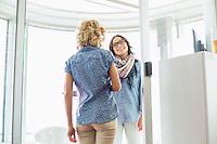 Happy businesswomen conversing in creative office