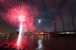 © Licensed to London News Pictures. 08/09/2014. London, UK. A tall ship on the River Thames is illuminated by fireworks and a full harvest moon outside the Old Royal Naval College in Greenwich on the evening of 8th September 2014. The Royal Greenwich Tall Ships Festival takes place in London from 5-9 September 2014. Photo credit : Vickie Flores/LNP