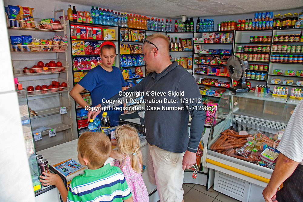 Purchasing water, cola and snacks at a small Polish convenience grocery store sklep. Krolowa Wola Central Poland