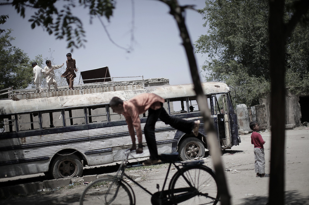"""Afghan boys (L) play atop of a destroyed Soviet bus parked outside the ruins of a compound, which use to be home to a timber manufacturing factory in the late 80's, on the western outskirts of Kabul on May 14, 2010. Two NATO soldiers fighting in Afghanistan to quell a Taliban-led insurgency were killed in attacks, the military said. One was killed in an """"insurgent attack"""" in the east of the country and the other died after a crude Taliban-style bomb exploded in the south on May 13, NATO's International Security Assistance Force said. AFP PHOTO/Mauricio LIMA"""