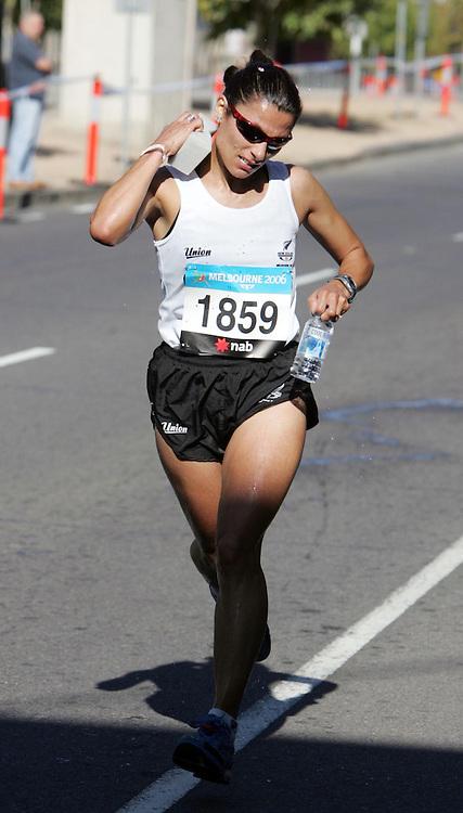 New Zealand's Liza Hunter Galvin cools down as she runs through the streets of Melbourne during the Women's Marathon at the XV111 Commonwealth Games,Melbourne ,Australia.Saturday, March 19,2006.Photo:Joe Mann/PHOTOSPORT. *** Local Caption *** Womens Marathon