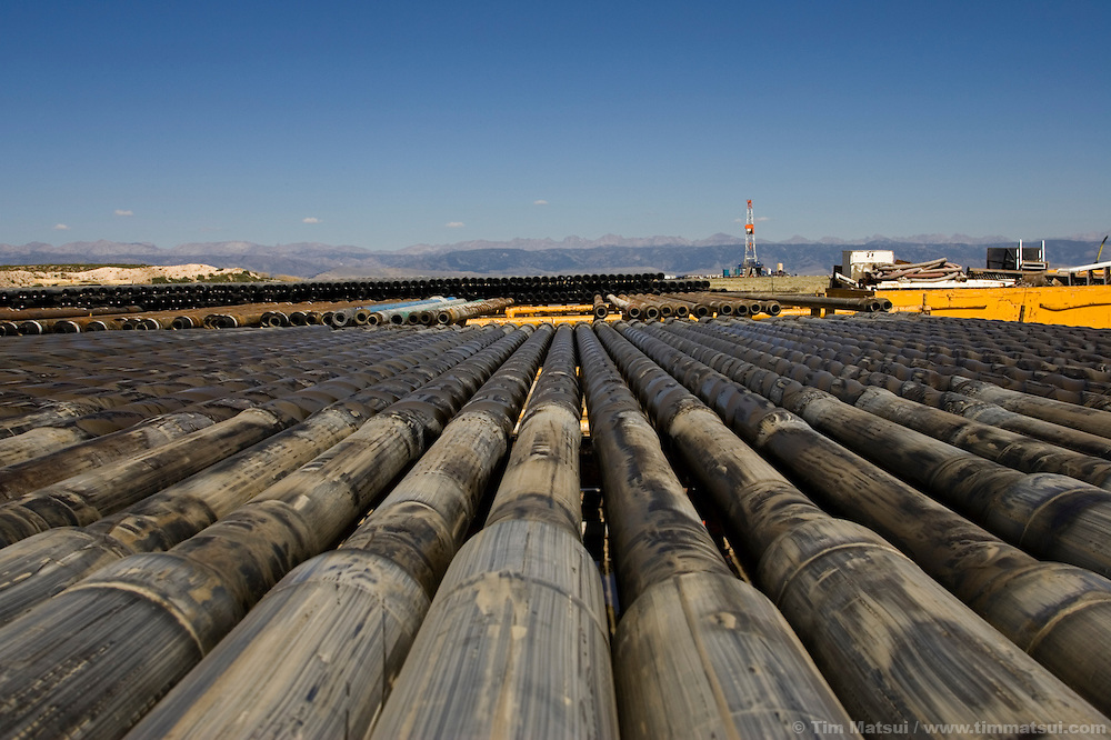"PINEDALE, WY - Racks of drilling pipe for Caza drill rig 86 on the Pinedale Anticline near Pinedale, Wy., (pop. 1400) on August 18, 2005. ""We're doing our best to keep the Californians from freezing to death in the dark,"" jokes company man Chris Holten, who has been an engineer in the petroleum industry for years. Questar, one of the main natural gas lease holders in Sublette County, which encompasses the Jonah Field, was recently granted approval for year-round drilling operations in the Pinedale Anticline, an environmentally sensitive winter forage ground for big game, part of the longest big game migration route in the lower 48, as well as hosting the largest remaining population of sage grouse. Some of the reasons for approval were Questar's proposal of fewer drill pads, more directional drilling, and a pipeline to transport condensate and water out of the environmentally sensitive areas. Critics say these changes should have been standard in the initial drilling permit which, were it to be followed, would have amounted to a greater overall environmental impact than the newly approved plan. Year-round drilling will allow the company to develop its wells in about half the time (10 years vs. 18 years) and to stabilize a seasonal influx of workers, allowing contracted employees to take up residence in the area instead of spending the summers in company man-camps or the area hotels. In the nearby Jonah Field where operators are seeking an 'in-fill' project with the number of cheaper straight-down wells increasing from 533 to 3100, Encana, one of the chief operators, is expected to drill two thirds of the wells to yield upwards of 10.5 trillion cubic feet of natural gas which has a current market value of $55 to $60 billion dollars. Encana could make $2 billion in profit per TCF depending price trends and production costs. Amongst Pinedale Anticline engineers there is already talk of in-fill projects and deep wells reaching down to 20,000 feet. Current wells are in t"
