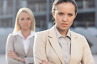Portrait of serious young businesswoman with female colleague in background