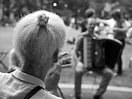 Man with braided grey hair watching an accordeon player in Bryant Park