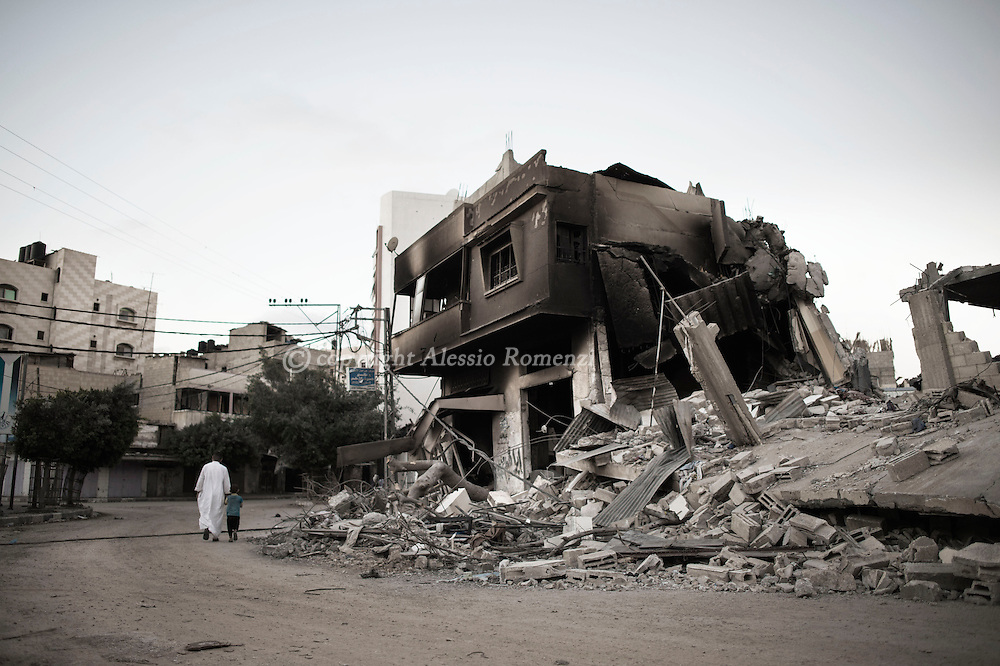 Gaza Strip, Gaza City: Palestinian walk in front of a house destroyed by an Israeli airstrike on August 8, 2012. ALESSIO ROMENZI