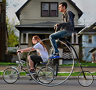"Spanning much of the history of the bicycle, Cameron Austin, 23, right, rides his replica 1875 Penny-Farthing ""high wheeler"" on East Broadway with his brother Tanner, who cruises on his customized 2005 Low Rider brand bike he calls ""Black Beauty."""